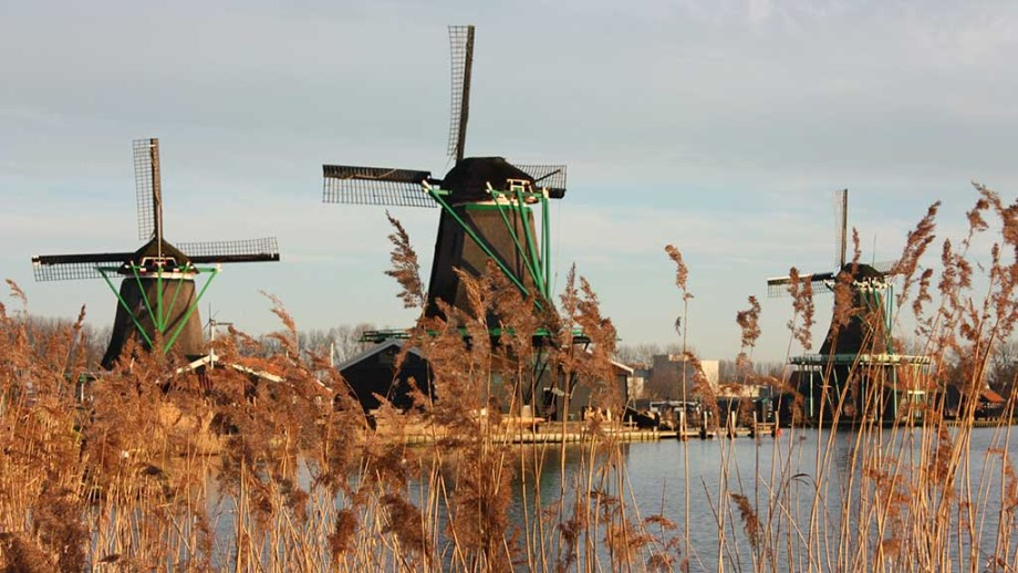 symbol of a tradition now lost, now a mere tourist attraction. colorful windmills built of wood still overlook the water of the river of zaanse schans on which it reflects their vintage image
