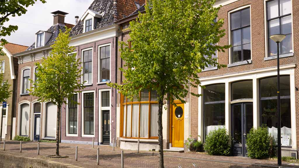 View on canal houses on a cobblestoned street in the city of Franeker, Friesland, The Netherlands