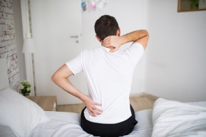 man holding back at the edge of bed due to pain