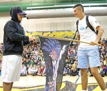Coby Petau hands the MV Unit flag off to incoming senior Judd Erickson.