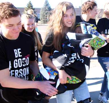 Sophomore Maya Winslow and senior Sam Atlas carry Super K, bundled up, to the middle school.