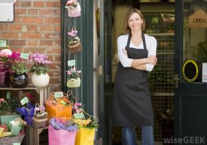 smiling-woman-standing-outside-flower-shop