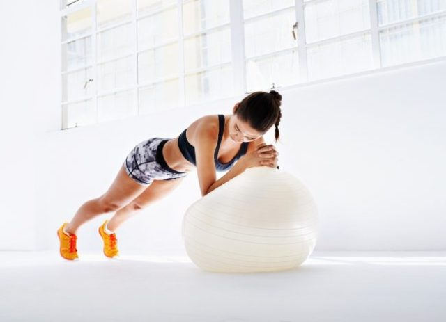 Fit Woman Doing Plank on White Exercise Ball – 1 of 5 Exercises for Abs You Should Add to Your Ab Workout Routine | Vitacost.com/blog