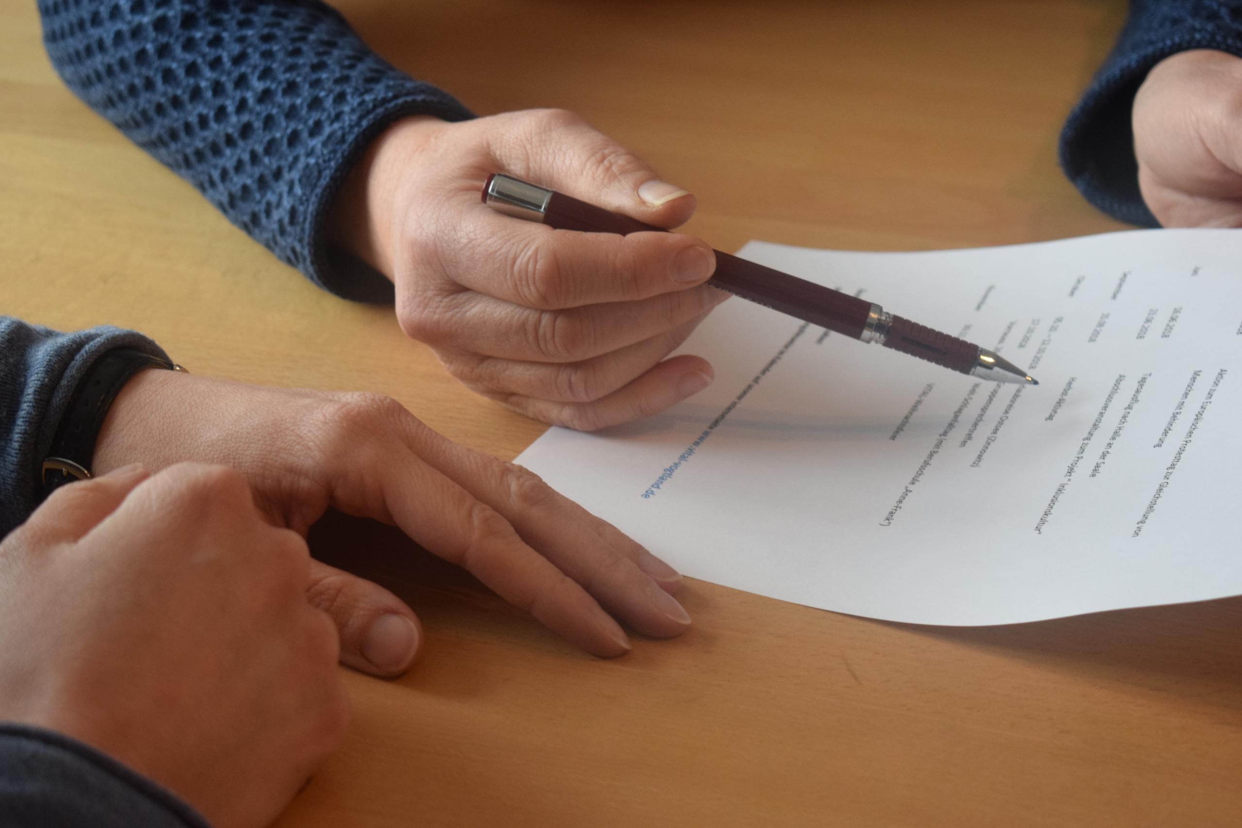 Die Hand der Beraterin deutet mit einem Stift auf ein Formular.