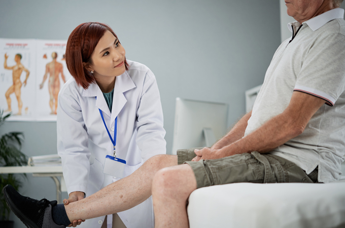 Senior patient telling doctor about pain in his leg