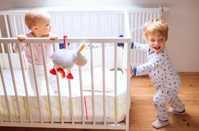 Two happy toddler children in bedroom at home. A girl in a cot and a boy standing on the floor.