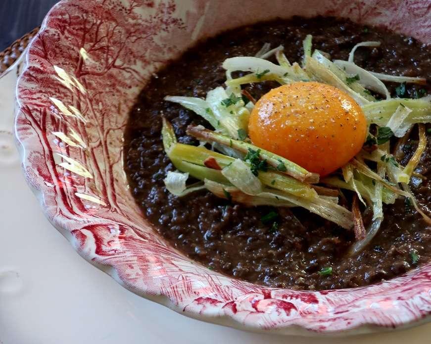 zuppa di lenticchie nere con uovo marinato e porro fritto