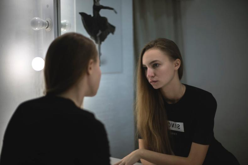 ragazza che si guarda allo specchio con insoddisfazione