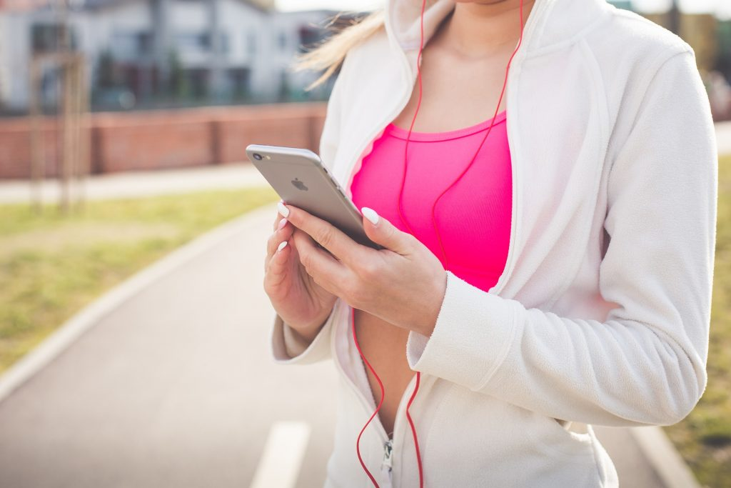 fit woman wearing pink top and white jacket holding a phone with red earphones getting ready for a run background street, effects of music on exercise, 5 Ways Music Affects Your Workouts