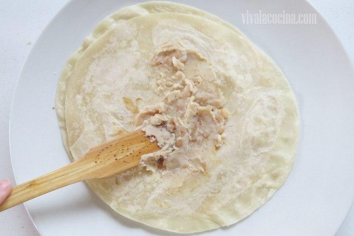 Colocar un poco de los frijoles refritos y extender por la tortilla