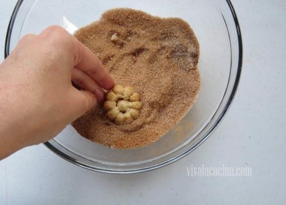 Pasar las galletas por el azúcar con canela
