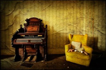 Harmonium and yellow armchair, derelict Manor House 'B', Norfolk, UK