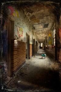 Child's toy pram in corridor, with murals, windows and doorways, derelict Hellingly Asylum, West Sussex