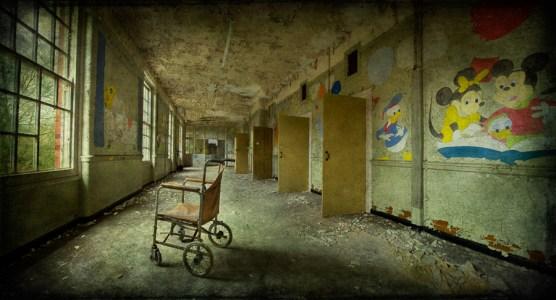 Wheelchair in corridor, with Disney murals, derelict West Park Asylum, Epsom, Surrey