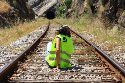 Ângela Rego a ser fotografada enquanto fotografa um troço de caminho de ferro à entrada de um túnel.