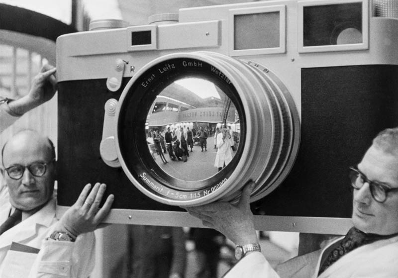Black and white photo of two men carrying a large model of a camera
