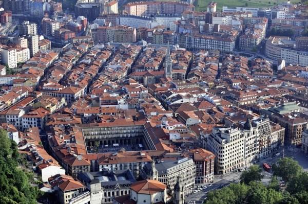 La Plaza Nueva de Bilbao, uno de los principales atractivos de Bilbao, esta plaza construida en 1849 fue cantada por don Miguel de Unamuno y se destaca por su elegancia. Ubicada en el Casco Viejo, en la zona peatonal declarada Monumento Histórico-Artístico, planta cuadrada y el cuerpo de tres pisos con balcones, sostenido por 64 arcos separados por columnas dóricas. Fue la primera plaza de la ciudad, su nombre original era Plaza de Fernando VII y en ella funcionaron importantes instituciones públicas, convirtiéndola en su momento de esplendor, en el centro cívico y comercial de la ciudad. En su centro lució una estatua de don Diego López de Haro, luego trasladada a la plaza circular; un quiosco de música y una fuente de dieciocho surtidores que arrojaba agua a siete metros de altura. Actualmente es la sede de la Academia de la Lengua Vasca y los domingos alberga un animado mercado donde se entremezclan pájaros y otros animales pequeños, sellos, monedas, antigüedades, cosas usadas y otros objetos de los que fascinan a los coleccionistas. Las fiestas religiosas son buenas excusas para darse una vuelta por la Plaza Nueva: cerca de Navidad se celebra el Mercado de Santo Tomás, actualmente transformado en Concurso Agrícola por la BBK, cuando miles de personas se reúne para degustar talo con txorizo y sidra, y en la víspera de Todos los Santos el Mercado de coronas y ramos de flores. Y luego, unos pinchos y rabas en alguno de los muchísimos bares y cafés de la zona