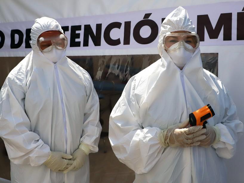 Médicos voluntarios vestidos con un traje, máscara, guantes y gafas protectoras en una carpa instalada para evaluar a personas por Covid-19 en Monterrey.