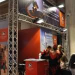 CHRISTIAN TOUR - Stand expozitional personalizat cu structura din grinda de aluminiu cu zabrele, pupitru info personalizat, scaune de bar, podium iluminat in cant, reflectoare cu lumina rece, grafica de stand personalizata.