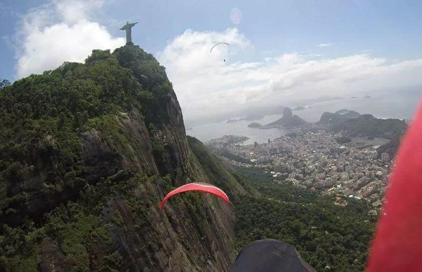 A person flying a paraglider on a grassy hill - Pedra Bonita