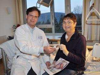 Dr. med. Jürgen Heyne übergibt Patientin Carmen Müller den Info-Patientenpass