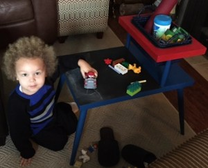 Ryker sits next to his new table and plays with a truck. Chalk is laid out on the chalkboard top.