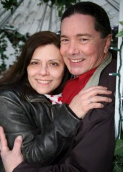 A closeup of us in a hug. I'm wearing a leather jacket and Derek has riding gear on including a red bandana around his neck.