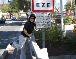 I'm wearing a helmet and have my arm around the sign for the town of Eze, France