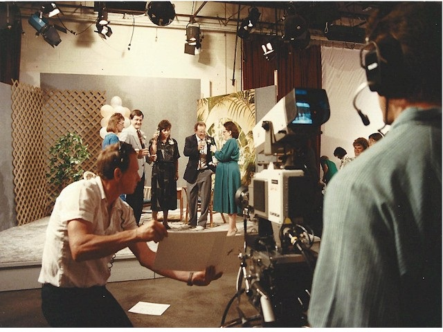 Shot of the riser with me and a few others toasting with champagne, with the backs of a camera man and director in the foreground