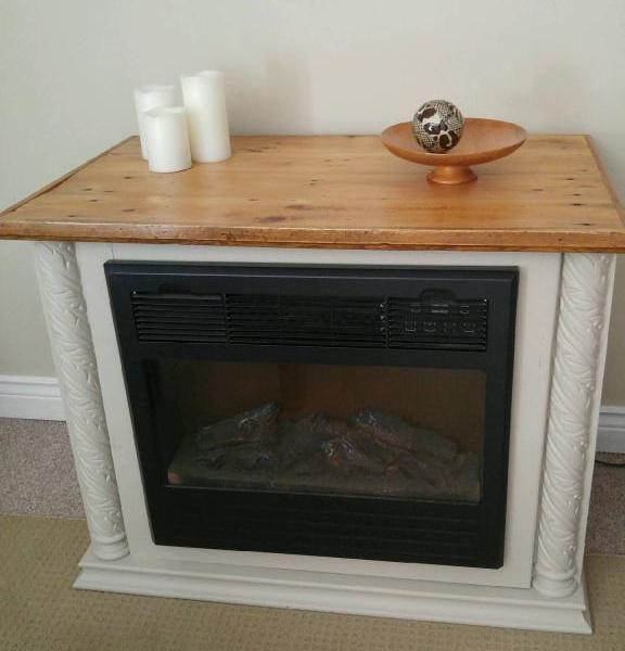 finished fireplace surround done in a creamy beige with a varnished barnboard mantle.