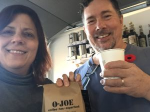Derek and I hold up our coffee cups in salute, and a bag of O-Joe beans.