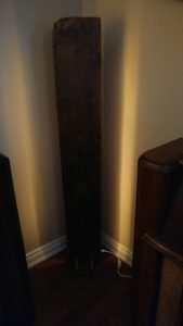 four foot tall piece of barnboard gives off soft light on either side. Rope lights ae sandwiched between the barnboard and a backing board and standing on stained feet.=