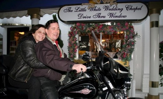 Derek and I on a black Harley in front of a sign that reds the Little White Wedding Chapel Drive Thru Window