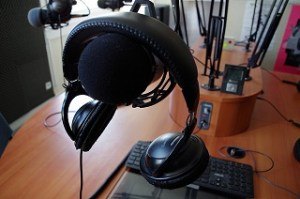 headphones resting on a microphone in a broadcast studio