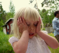 Little girl outside on a summer day holding her head in her hands and screaming in frustration
