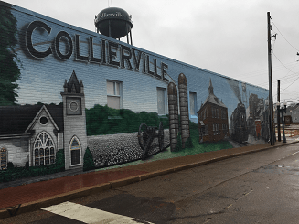 Collierville mural painted on the side of a brick building shows a church, silos, and other old buildings