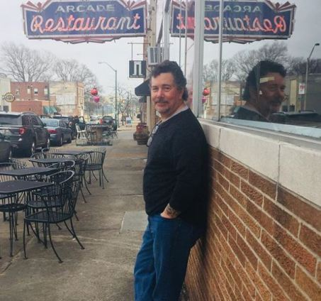 Derek leans against the brick wall of the Arcade restaurant as its neon sign reflects in the window above him