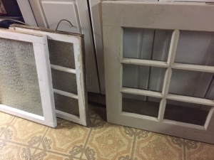 Three old windows of varying sizes leaning against a cabinet. Flooring is a wild, busy pattern in brown and yellow.