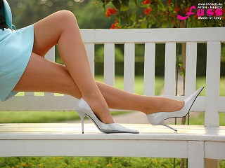 woman in pantyhose wearing white high heels and a blue skirt has her legs crossed