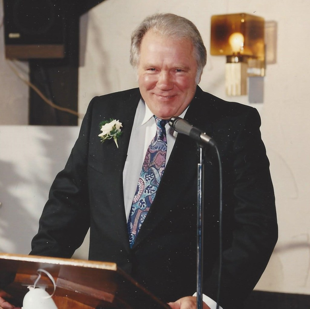 My Dad in 1993, at the podium making a speech at my wedding, looking healthy and smiling wearing a dark suit and a yellow carnation on his lapel