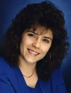 My headshot from the early 1990s. I have huge, curly hair, big hoop earrings and I'm posed in the classic head-tilt