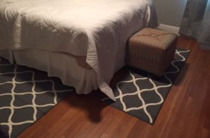 End of the bed shows a rug at the end and one at one side - both are grey with white lattice patterns