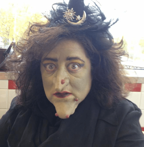 Closeup of a witch - long frizzy black hair, giant chin, green skin and a huge wart on her nose