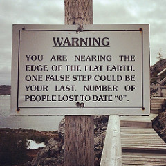 Sign reads: WARNING! You are nearing the edge of the flat earth. One false step could be your last. Number of people lost to date: 0.