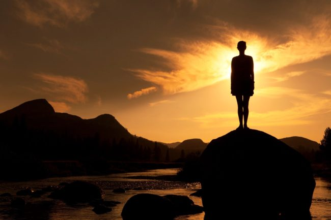 silhouette of a person standing on a rock with the sunset in front of them