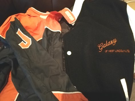 Dad's riding jumpsuit is black with an orange collar and orange J. His Galaxy of West Lincoln jacket is a black wool bomber-style with orange lettering
