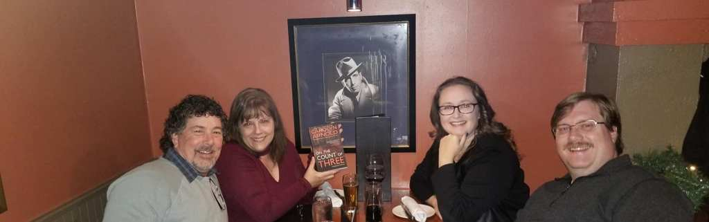 The four of us at our table at the Keg in front of picture of Humphrey Bogart. I'm holding up a paperback of Carolyn's new book.