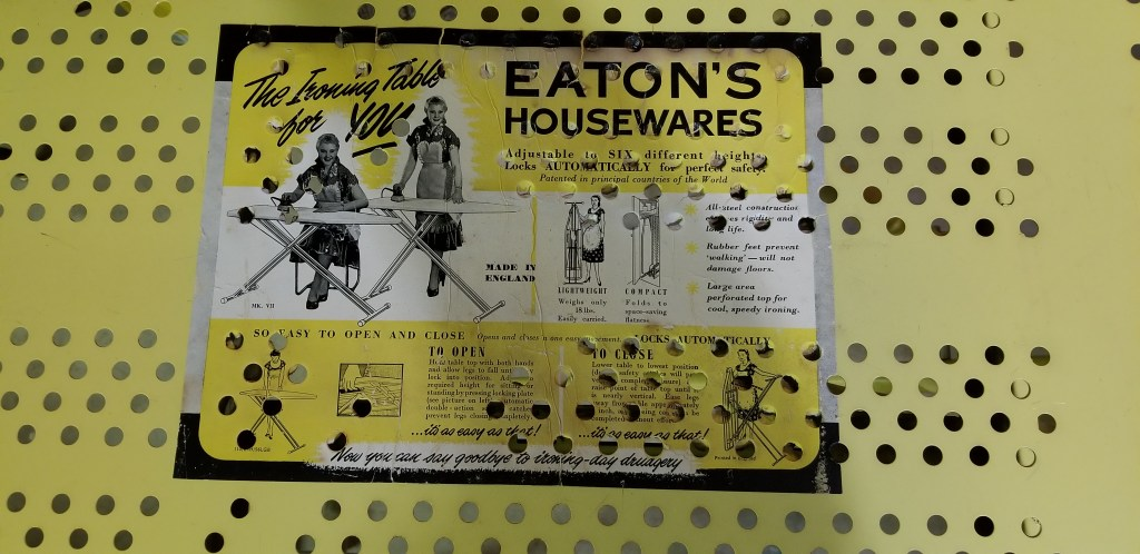 Yellow metal ironing board has an old-fashioned Eaton's Housewares sticker on it. A happy woman in a fancy dress is shown ironing while sitting or standing! Other features of the board are listed with diagrams and drawings.