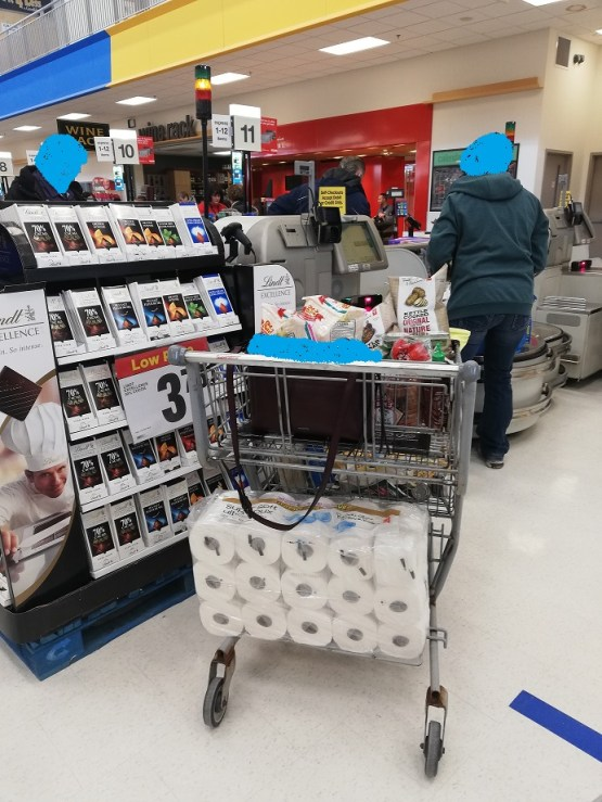Woman fussing with bags at the self checkout while her purse sits open and unattended a good eight feet behind her, in the shopping cart. She has a massive package of toilet-paper rolls on the rack of the bottom of the cart.
