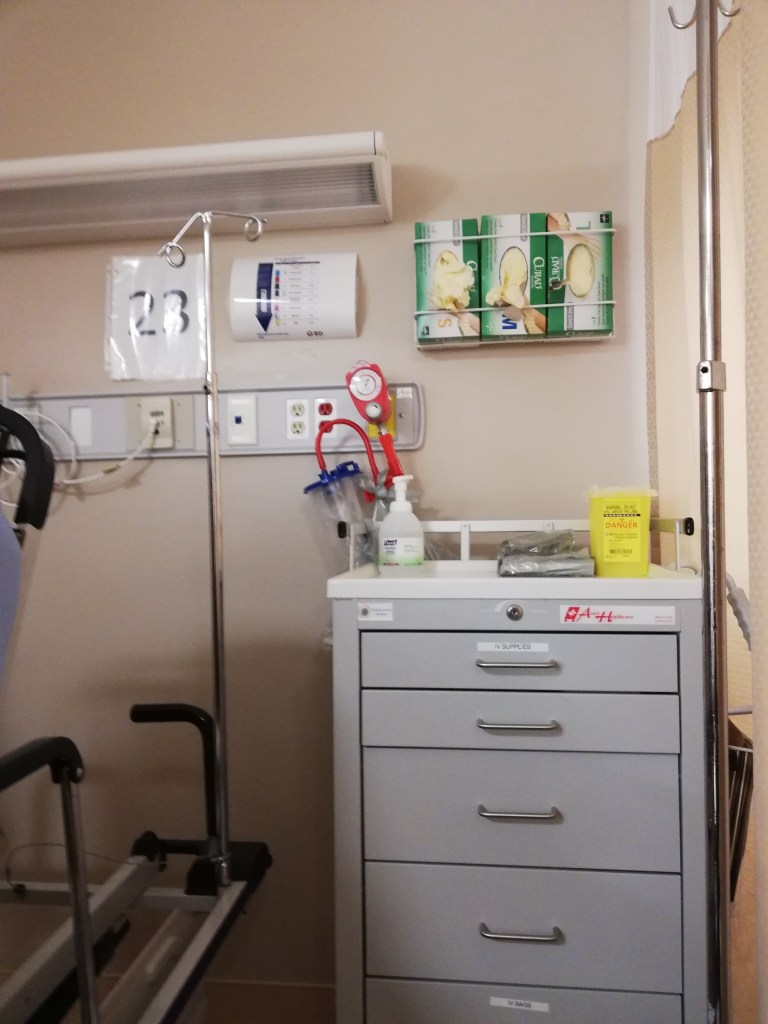 A hospital bed, dresser, boxes of gloves and all of the other doodads you see in a hospital room.